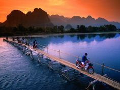 People Crossing Bridge Across Nam Song River by Motorbike, Vang Vieng, Laos: 18x24 Photographic Print