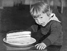 San Francisco, California 1934.A young boy licks his chops in anticipation of eating a piece of cake.