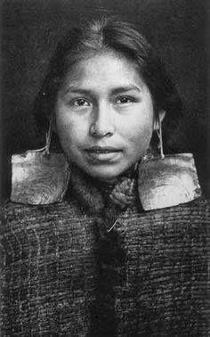 A Kwakwaka'wakw girl wearing abalone earrings and a cedar bark cloak, circa 1914. by Edward S. Curtis