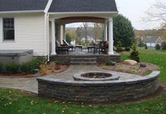 Love the covered porch and stone patio with fire pit.