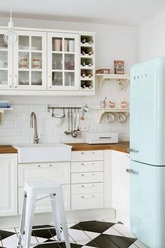 White country kitchen with Belfast sink, duck egg blue fridge, painted wooden flooring