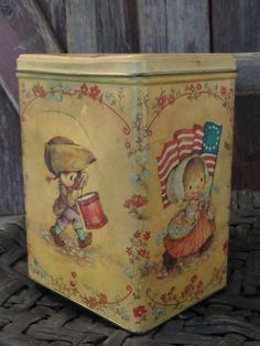 "This vintage tin was made by ""Hallmark Cards, Inc."". There is no date on the tin, but from the scenes depicted on the sides, I believe it was for our Bicentennial Celebration in 1976."