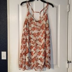 Tilly's Peach Floral Tunic Top Happening in the Present brand, bought at Tilly's. Light chiffon floral printed fabric with a lining, tunic length, cage straps in back. It has an area where the fabric wasn't pulled all the way straight when they sewed the trim, it came that way, see picture 2. It's not noticeable at all! I sewed the outer set of straps tighter because they fell off my shoulders but I kept the length and didn't cut them. EUC! Tilly's Tops Tunics