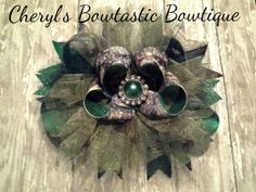 Moss Oak Over the Top Bow with Black Marabou feathers and Green pearl jewel. This bow is Very Large around 6 1/2 inches wide and 4 1/2 inches tall.