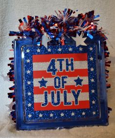 """This is a beautiful Glass Block 8x8x3 featuring 4th of July on wooden sign with red, white and blue """"garland"""". This block is ideal for July 4th. The price shown is for the block as it is shown here, h                                                                                                                                                                                 More"""