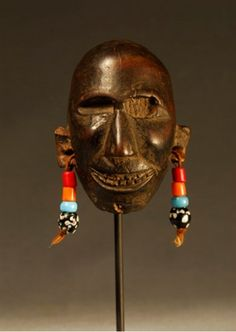 A small wooden Naga mask that would have once been worn around the neck. It measures 9 cms in height, is black in colour, and has four coloured beads attached to holes in each ear-lobe.    The Nagas, Hill Peoples of Northeast India, feared for taking trophy heads. Little did Michael Yates know when he bought two Naga objects.