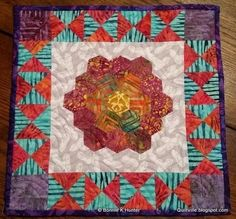 """A hexagon may seem like a complex shape compared to triangle quilt patterns, but this Hexagon Mini Quilt Pattern is gorgeous and pretty easy to make. You must know how to do the English <a href=""""http://www.favequilts.com/tag/Paper-Piecing-Patterns"""" target=""""_blank"""">paper piecing method</a> in order to follow this quilt tutorial. The border is pretty simple because it's made of triangles, but the hexagon rosette in the center is where the real beauty lies. This &..."""