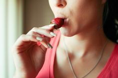 Image-girl is touching strawberry from her lips