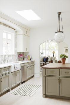 Modern kitchen with retro lighting, creme cabinets, and checkered backsplash