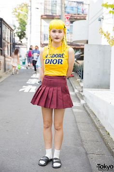 his is Noa, a friendly girl with yellow braided hair that caught our eye on the streets of Harajuku. We learned that she's 19 years old and she works in sales/marketing. She is wearing a yellow J'adore Dior top, with a pleated mini skirt from Bubbles Tokyo. Her sandals are from Nike, worn with white socks. (Tokyo Fashion, 2014)