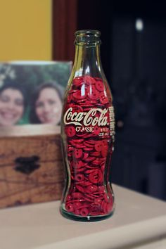 Coke bottle filled with red buttons.
