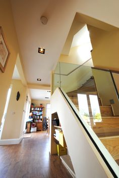 Glasgow Architects, Allison Architecture developed designs for a rear extension and loft conversion in Hamilton.   The main feature of the interior was this oak staircase which wraps up through the heart of the house and forms the backdrop for the new hearth.  The solid oak stair has a frameless glass balustrade and skylights above to allow floods of natural light to come down through the space.