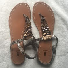Bakers Sandals Worn Bakers slip on sandals with cute bronze and silver scrunching. They are in used condition with some fraying on the straps and a spot on the left foot (as seen in the picture) and the bottoms are pictured Bakers Shoes Sandals