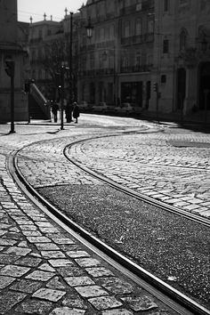 Rails cut a cobble stone road in the neighborhood of Alfama (Lisbon)  Quality photo print, available in different sizes