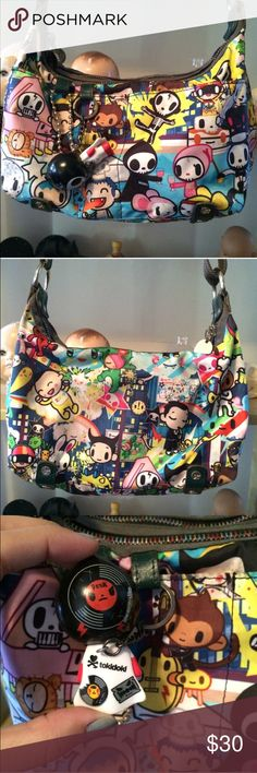 """Authentic Tokidoki Lesportsac bag Tokidoki Lesportsac bag 2009. I *believe* this is the Concerto Punk Sorriso or 2009 year version. Has multiple pockets and zippers and the original Qee figure. The outside of the bag is slightly dirty in some areas, but can likely be remedied with a good clean. Also, in the inside of the bag there are black pen markings. All the hardware on the back is in perfect condition. The Quee keychain does have scratches. Dimensions are approximately 11-1/2"""" W x…"""