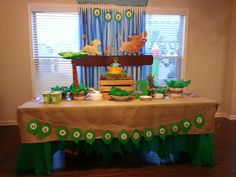 Lion King themed birthday party. Decor ideas. Hakuna matata backdrop. Burlap tablecloth. Waterfall made by braiding 3 plastic tablecovers (blue, light blue and white) Simba, Timon, and Pumbaa decals from Amazon. Cheetah print table runner. Leaf banner. Crate. Placed the decals on a foam board for a 3D effect.