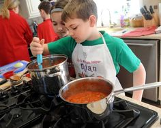 Eight-year-old Dylan Greenlaw stirs a pot of tomato sauce as his sister Alyssa, 10, peers over his shoulder Saturday, April 4, 2015, during a cooking class for kids taught by Debbie Barbiero at her home in Shelton, Conn. For more information on group classes and other services, visit http://metamorphosisbodymindspirit.com. Photo: Autumn Driscoll / Connecticut Post