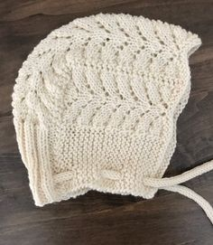 Free Knitting Pattern for Petite Pines Baby Bonnet - The Petit Pins baby bonnet has a lace pattern inspired by Norwegian Fir cardigan pattern by OGE Knitwear Designs. Free matching blanket pattern is available. Designed by Espace Tricot. Knit the blanket, bonnet, and sweater for a complete baby layette.