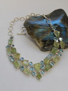 A stunning collar featuring an array of sparkling polished faceted green-hued Prehnite gemstones, accented with faceted London Blue Topaz gemstones, set in 925-hallmarked sterling silver. Length: 16-1