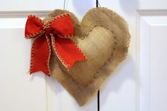 This heart is made of burlap, finished with a red bow, and is hung by black wire.