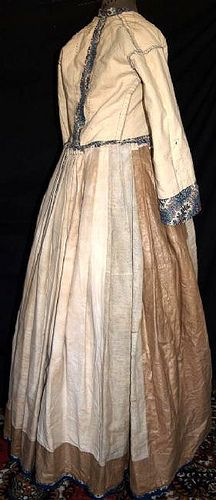 """Interior 1860's roller printed gown. Orange, Red & Blue floral sprays on cream wool challis background. Mostly hand sewn. Piped at waist & armscyes, has original brass hooks with handmade round eyeholes. Bodice fully lined with cream linen and openings are lined with brightly printed calico. Skirt has cartridge pleating, hem edged with blue hem protector, has deep right side pocket, skirt lined with cream & brown polished cotton. Bust: 30""""; Waist: 22""""; back length of gown: 57""""."""