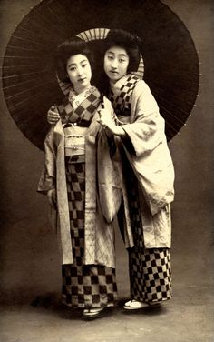 Two Bijin wearing Haori 1920s § Bijin (Japanese Beauties) wearing Haori (kimono-shaped jackets) and holding a Bangasa (large oil-paper umbrella). This postcard is by Kamigataya Ginza in Tokyo, which specialised in emotive portraits of actors and actresses. Haori were 'all the rage' in women's fashion during the Taisho period (1912-1926).