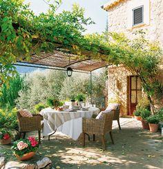 Comedor exterior bajo una pérgola recubierta de vegetación. Comedor de exterior rústico con pérgola