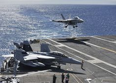 """An F/A -18F Super Hornet from the """"Black Knights"""" of Strike Fighter Squadron (VFA) 154 lands on the flight deck of the aircraft carrier USS Nimitz (CVN 68) while an EA-18G Growler from the """"Gray Wolves"""" of Electronic Attack Squadron (VAQ) 142 stands by."""