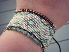 This listing is for a handmade, loom woven cuff bracelet. The bracelet is created with high quality beads and genuine leather cording. The bracelet is woven with a high quality nylon thread that resis