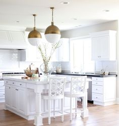 """To maintain the cool, fresh feel of the bright kitchen, we painted the walls with Silver Drop by Behr. I updated the kitchen nook with new pillows and installed European white oak floors."""