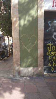 Corazon amarillo en una pared verde