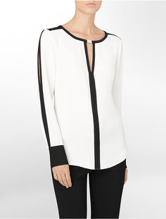 Color block blouse, v-notch neck with trim, back yoke with box pleat, button sleeve cuff, cold shoulder sleeve with tack closure at elbow, shirt tail hem.