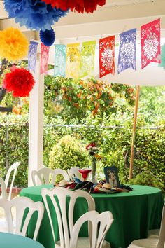 """Bright Colored Linens with """"Papel Picado"""" and PomPoms added a perfect touch for a Fiesta Themed Party!"""