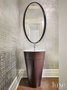 We love the bold simplicity of this powder room featuring an oval mirror by Christopher Guy, from @RADesign/Beacon Hill and the crosshatch wallcovering is Weitzner's woven silver metallic.