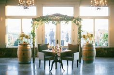 Create your oasis!  This sweetheart table is framed by a beautiful arbor and wine barrels and flowers - simply stunning for a vineyard wedding