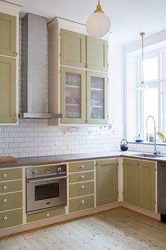 Måttbyggt kök i sekelskiftesstil, målat med linoljefärg i kulören Ljus Oliv. Som stänkskydd sitter Half Tile-kakel i tegelförband, kulör Brilliant White. Överskåpen har infällt musslinglas och lådorna är försedda med porlinsknoppar medan luckorna har skåpsvred i förnicklad mässing.