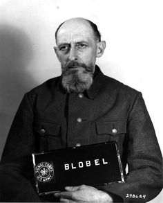 Paul Blobel at the Nuremberg Trials, March 1948. In 1943 to hide a massacre or to simply remove an eye sore, he ordered the bodies of Jews in a ravine to be removed, burned, and then had their charred bodies buried. Jews whom had been waiting to be murdered were tasked with removing the bodies and taking them to furnaces made of tombstones. When this was complete it was again the Jews waiting to be murdered that had to buried the charred bodies.