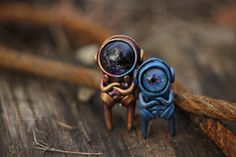 Wanderers cosmic expanse. They roam along the Milky Way, and the glasses of their helmets reflect the depth of the cosmos. Pendants made of polymer clay, glass helmets - glass beads.