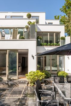 This imposing, flat-roof, 3-storey structure overlooks a landscaped garden with ornate topiary through walls of full height, bi-fold glazed doors and frameless balustrade balconies.