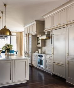 The mix of warm metal and cool paint colors on the cabinet were the perfect recipe in this kitchen design - Tobi Fairley Interior Design