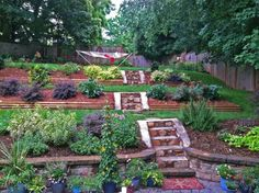 This is a great concept that leads up to a hammock! Or in this case, paradise! It's a super cute idea that even holds tiny little staircases along your trek. The short retaining wall adds character to each layer of this garden and stacks one on top of the other for a clean landscape. This is a perfect example on how you can do so much with so little. The varying sizes, shapes and colors of plants only adds more charm to the whole scene.
