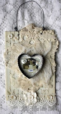 Mixed-media collage handcrafted on canvas with vintage laces, buttons, and pearl pins, vintage ephemera, and a vintage image set in a vintage heart-shaped tart tin.  This piece was created in tribute to the 20 young children who lost their lives in the unspeakable tragedy in Newtown, Connecticut, on 12-14-12.