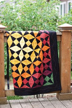 Designer Terry Albers created a brilliant kaleidoscope effect in her quilt by using gradations of yellow, orange, and red, with defining corners in green.
