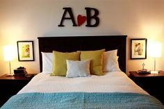 Spouses' initials above the bed with a heart in between + wedding photos above the nightstands