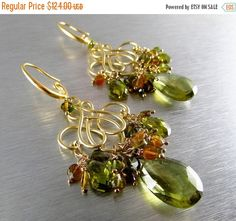 Perfect color combo for Fall! These beautiful eye catching gold plated chandelier earrings feature pretty olive free quartz briolettes, highlighted by dozens of faceted coin shape green tourmaline. On either side of the olive quartz are green cz briolettes. I have used gold filled wire and head pins. The satin finished swirl frame work is made of gold plated brass, along with the coordinating swirl ear wires.  The earrings measure 2 1/2(64mm.) from the top of the ear wire. Considering th...