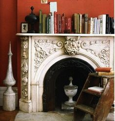 Ornate fireplace makes a natural focal point & pops against dark red wall