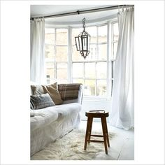 bay window, curtains straight across to allow more light, love the idea of something hanging in the center...