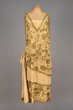 1920s BEADED EVENING DRESS, Sleeveless ivory silk having wrap front with side tie, angled draping and side streamers lavishly decorated in gold beaded floral, silk under-dress. Front