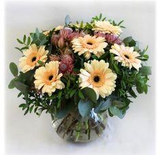 Blomsterhilsen med blomster i duse toner med grønt.