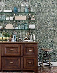 hex tile kitchen wall. glass exposed shelving. glasses well arranged. dark wood cabinets with only drawers. brick floor.